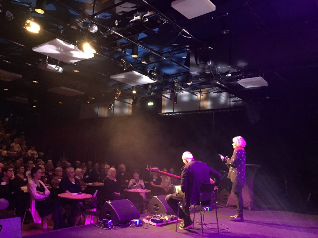 Marianne Folkedotter och Richard N Jokela på scen framför publik.